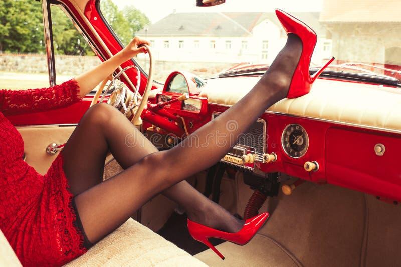 Den sexiga kvinnan hög-läker in sammanträde i retro bil arkivfoto