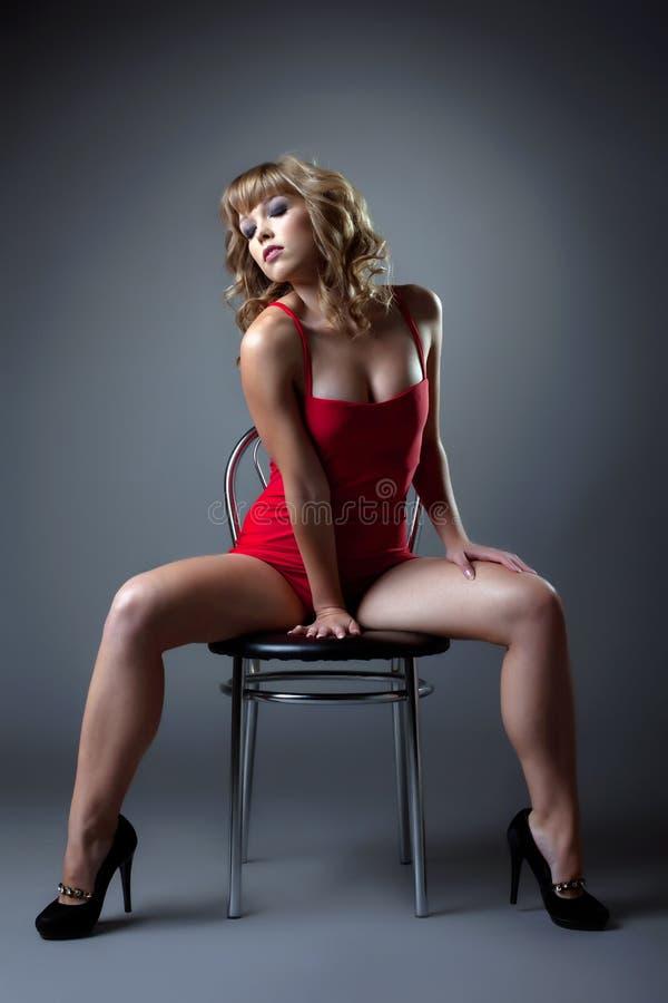 Den sexiga kvinnan i röd klänning sitter på stol royaltyfria bilder