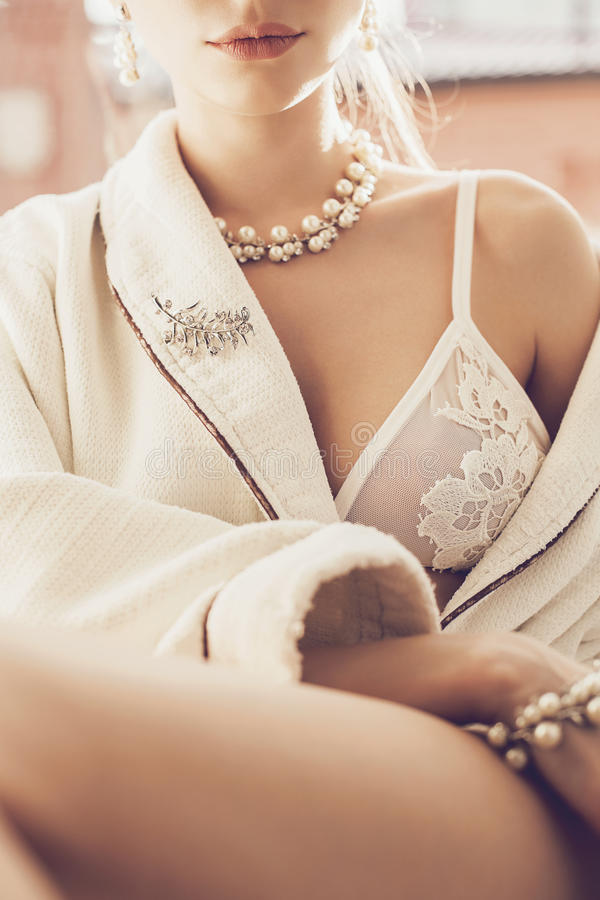 Den sexiga kvinnan i vit snör åt behån och smycken arkivfoton