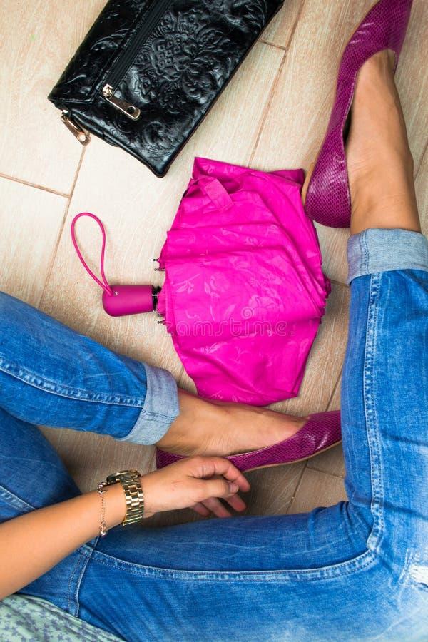 Den sexiga kvinnan lägger benen på ryggen på golvet med det rosa paraplyet arkivfoto