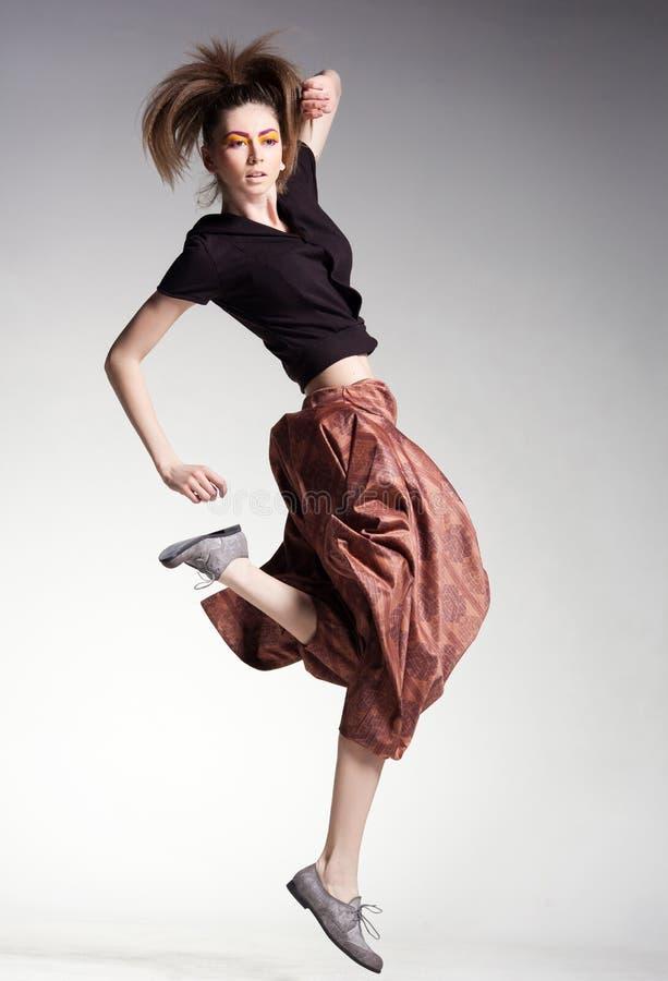 Den sexiga kvinnan modellerar banhoppning i stora flåsanden - boho-stilen danar arkivbild