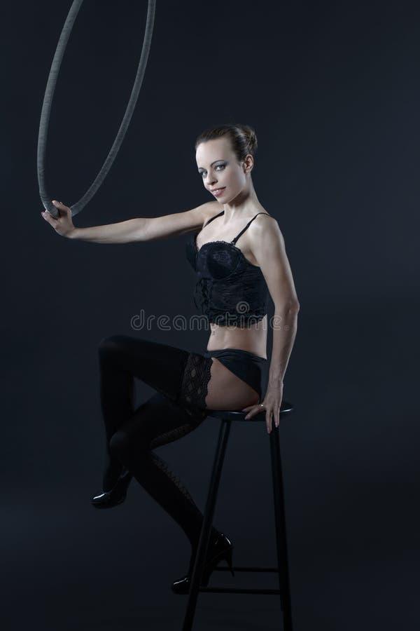 Den sexiga kvinnan sitter på stol med det flyg- beslaget royaltyfria foton