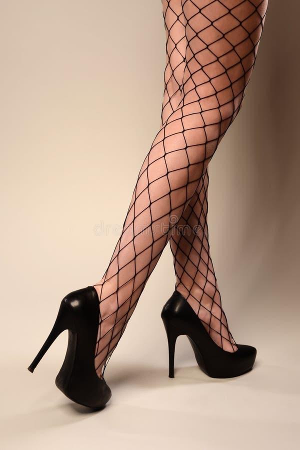 Den sexiga kvinnlign lägger benen på ryggen i netto strumpor som isoleras över grå färger royaltyfria foton