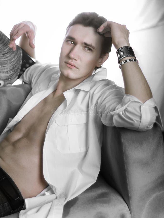 Den sexiga manliga modellen ligger bara på soffan i den knäppte upp vita skjortan som bort ser med förförisk blick royaltyfri fotografi
