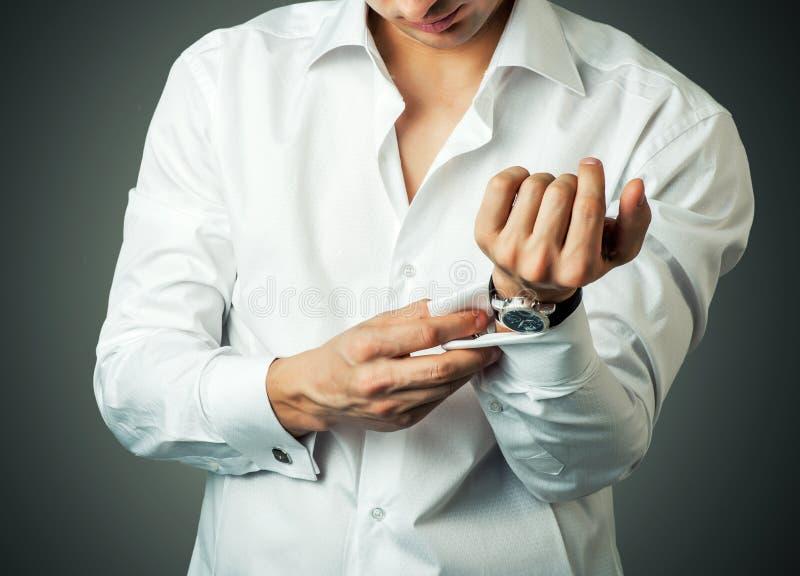 Den sexiga mannen knäppas manschettknappen på franska manschetter arkivfoton