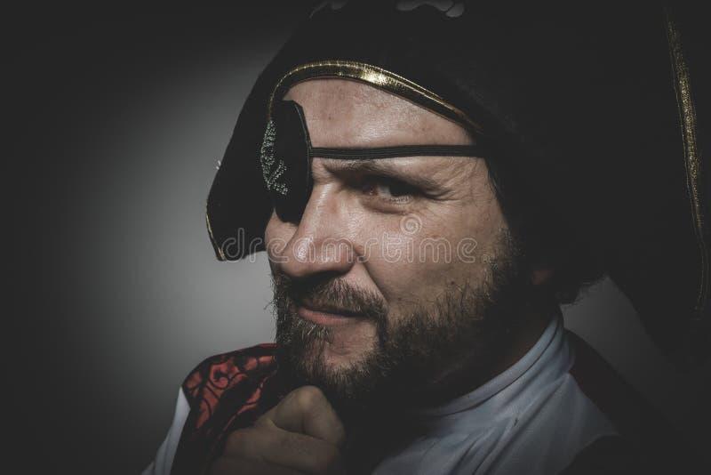 Den sexiga mannen piratkopierar med ögonlappen och den gamla hatten med roliga framsidor och royaltyfri fotografi