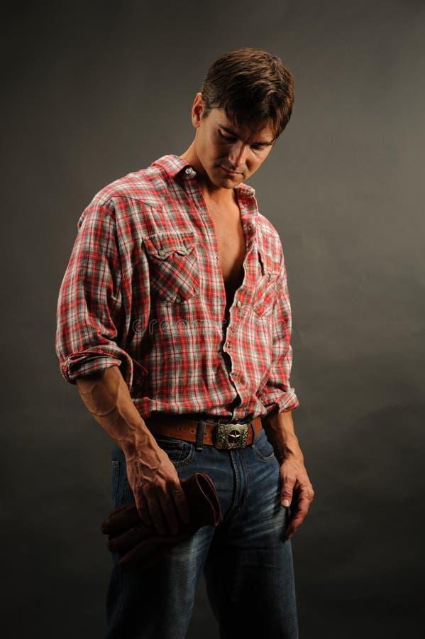 Den sexiga mannen poserar för ett fotografi arkivfoto