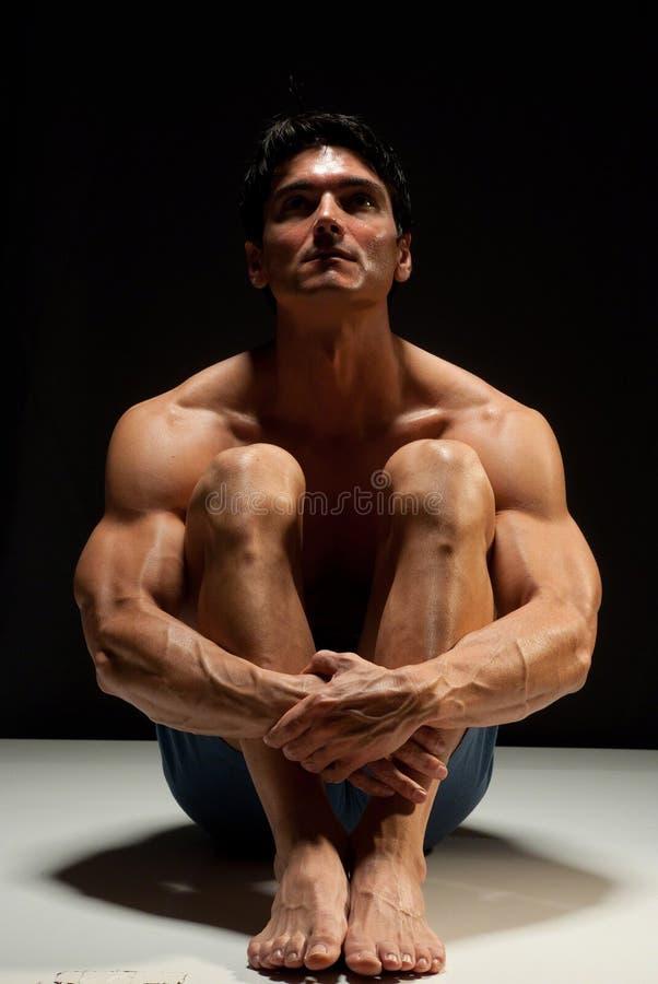 Den sexiga mannen poserar för ett fotografi arkivfoton