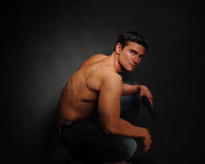 Den sexiga mannen poserar för kameran fotografering för bildbyråer