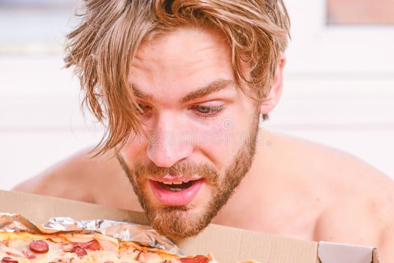 Den sexiga mannen ?ter pizza som ligger p? s?ng Studenten ?r hemmastadd p? s?ngen i en ljus l?genhet som ?ter en smaklig pizza Up royaltyfria foton