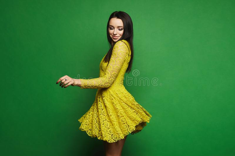 Den sexiga och trendiga brunettmodellflickan med blåa ögon och ljus makeup i kort stilfull gul klänning rotera omkring på grön ba royaltyfria bilder