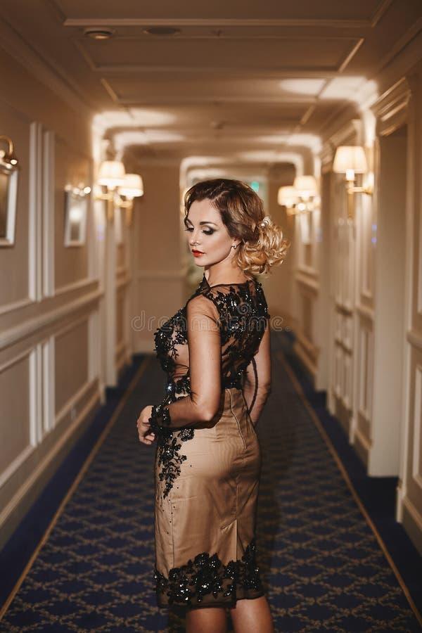 Den sexiga och trendiga unga affärsdamen med den moderiktiga frisyren och med ljus makeup, i stilfull klänning står på korridoren royaltyfri foto
