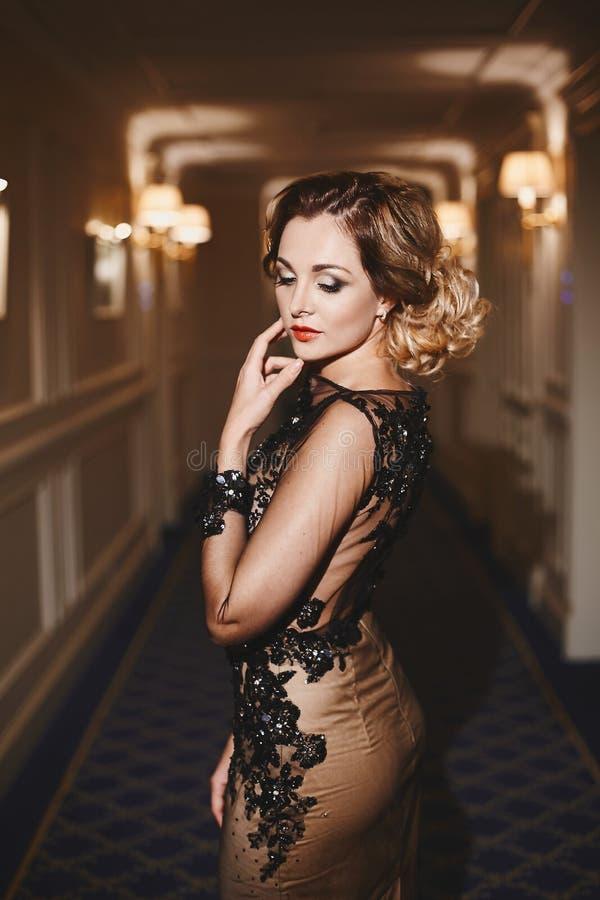Den sexiga och trendiga unga affärsdamen med den moderiktiga frisyren och med ljus makeup, i stilfull klänning står på korridoren arkivbild