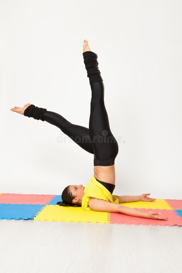 Den sexiga passformbrunettkvinnan i sportar bär i yoga poserar royaltyfri bild