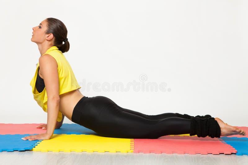 Den sexiga passformbrunettkvinnan i sportar bär i yoga poserar fotografering för bildbyråer