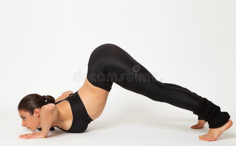 Den sexiga passformbrunettkvinnan i sportar bär i yoga poserar arkivfoton