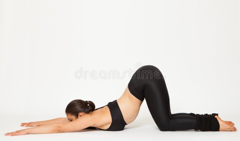 Den sexiga passformbrunettkvinnan i sportar bär i yoga poserar royaltyfria foton