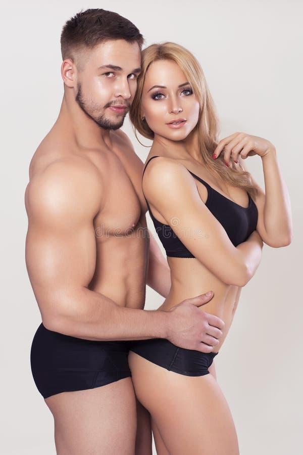 Den sexiga passformen tränga sig in par i sportswear på neutral grå bakgrund arkivbilder