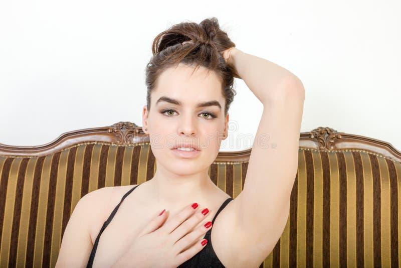 Den sexiga personen lyfter inomhus upp hår som ser förföriskt på kameran arkivfoton