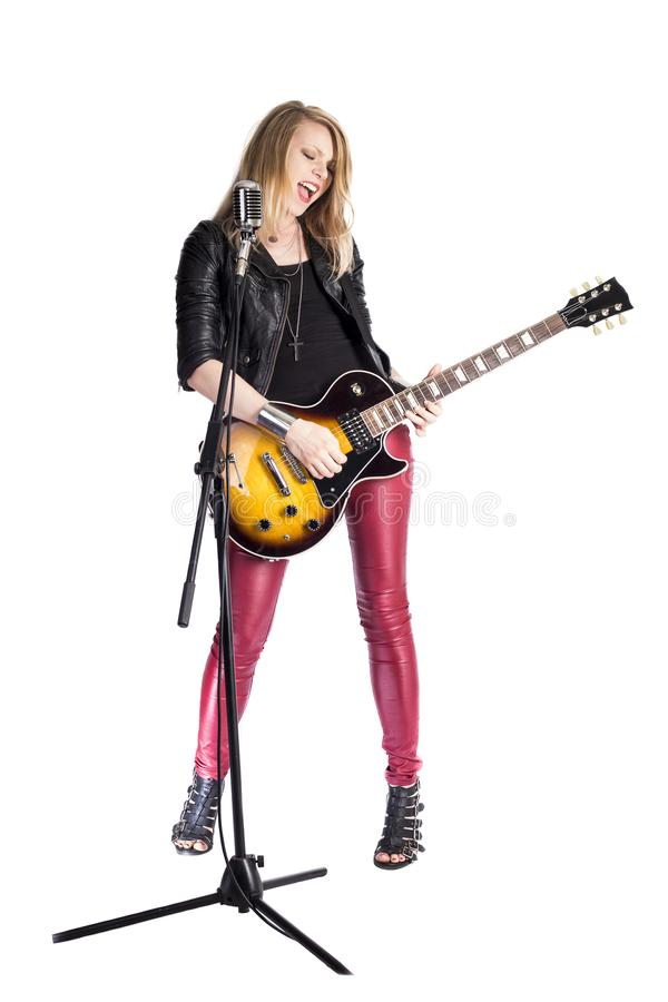 Den sexiga roliga blonda flickagitarristen spelar solo vid den elektriska gitarren, leenden, allsånger in i den retro mikrofonen  arkivbilder