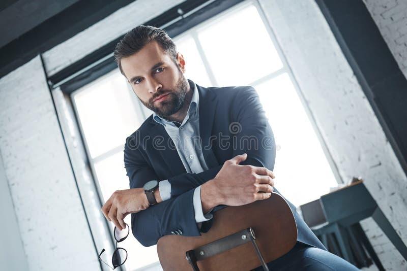 Den sexiga skäggiga mannen sitter på stolen på kontoret och ser mycket allvarligt på kameran arkivfoto