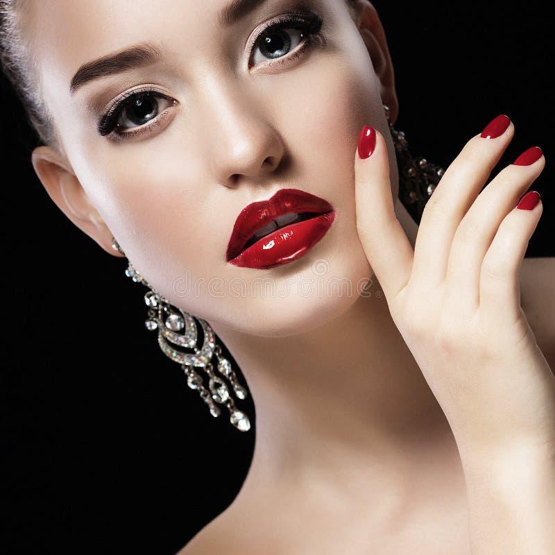 Den sexiga skönhetflickan med röda kanter och spikar Lyxig kvinna, smyckenörhängen sund makeup för härligt svart brunettmodehår arkivfoton