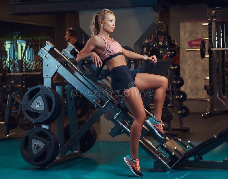 Den sexiga sportive kvinnan i sportswear ligger på ben trycker på maskinen i idrottshallen arkivfoton