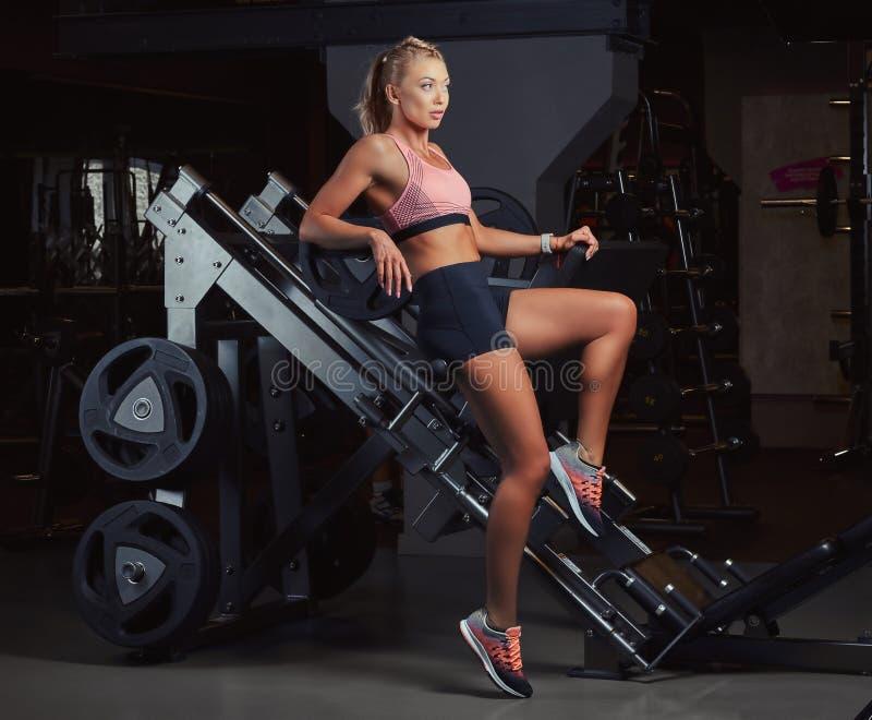 Den sexiga sportive kvinnan i sportswear ligger på ben trycker på maskinen i idrottshallen arkivfoto
