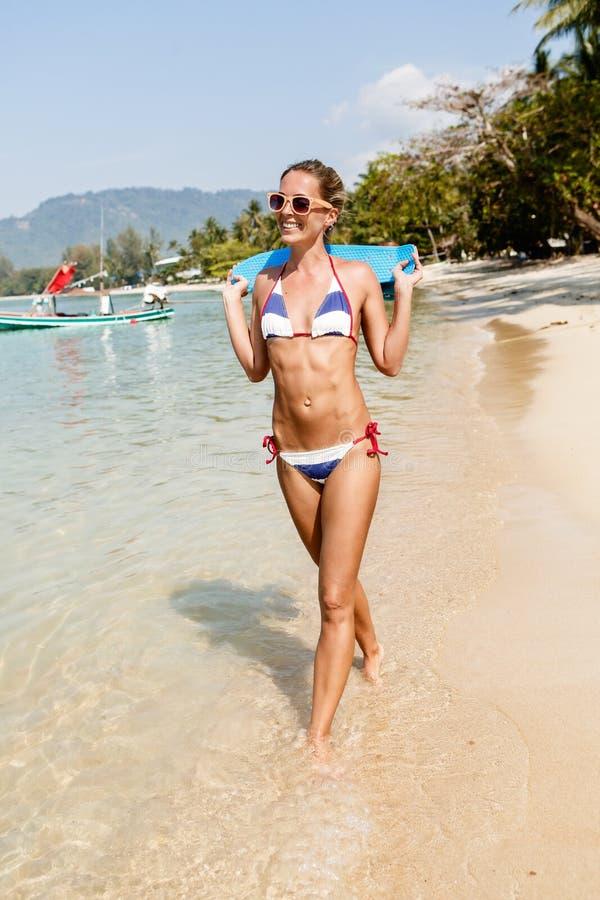 Den sexiga suntanned damen med det blåa encentmyntbrädet promenerar vara royaltyfri foto