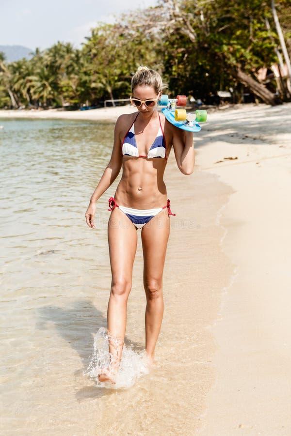 Den sexiga suntanned damen med det blåa encentmyntbrädet promenerar vara fotografering för bildbyråer