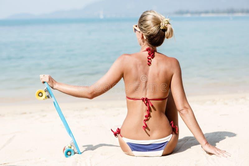 Den sexiga suntanned damen med det blåa encentmyntbrädet vilar på stranden arkivbild