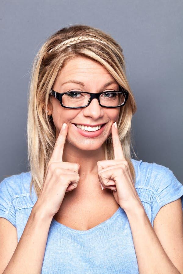 Den sexiga unga blonda kvinnan med fejkar leende för att visa framgång arkivbilder