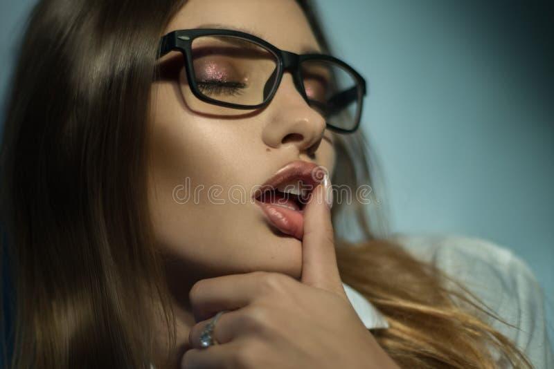 Den sexiga unga flickan med solglasögon tar hennes finger i mun med stängda ögon royaltyfri bild