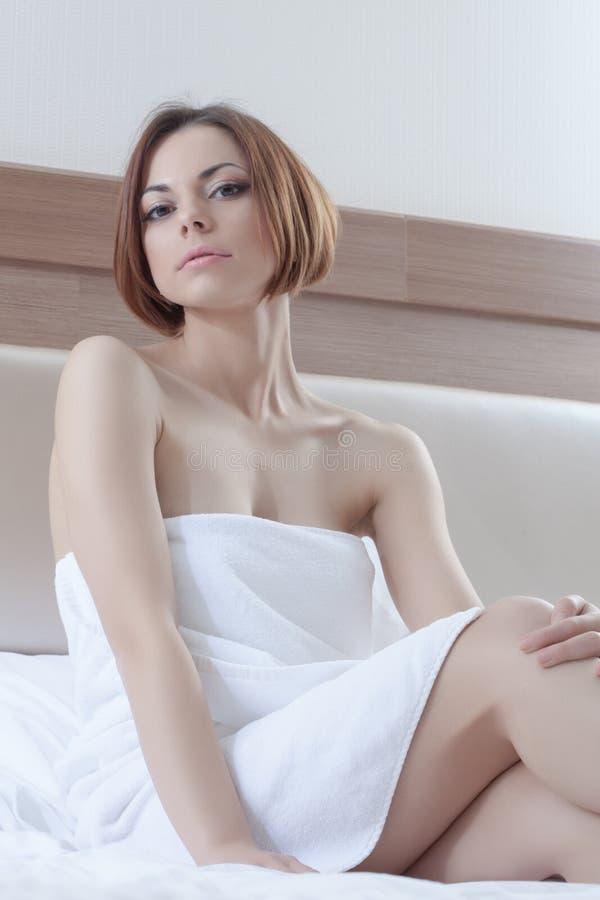 Den sexiga unga handduken för brunettkvinnawear kopplar av i underlag royaltyfria foton