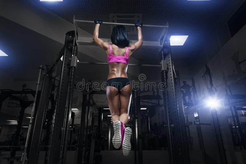 Den sexiga unga konditionflickan drar upp i idrottshallen arkivfoton