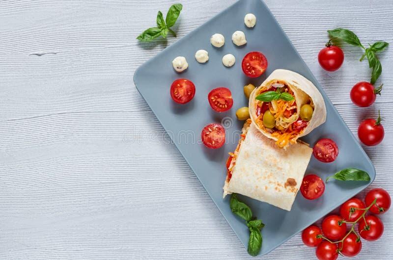 Den Shawarma smörgåsen eller lavashbröd med nya grönsaker och sås på den gråa plattan decotated med körsbärsröda tomater, basilik arkivfoton