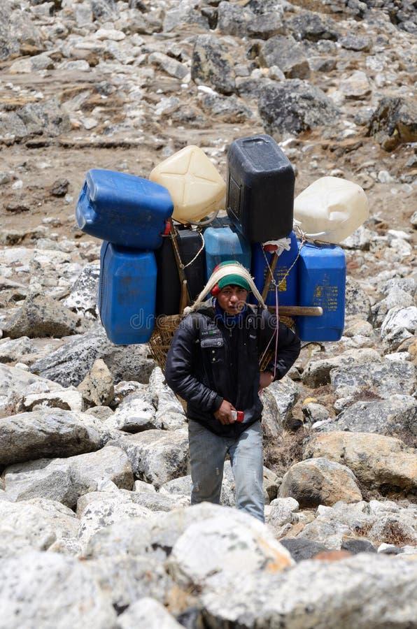 Den Sherpa portvakten bär den tunga påfyllningen i Himalayaen på den Everest baslägertreken, Nepal royaltyfria bilder