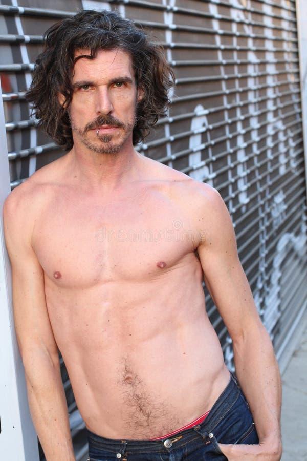 Den Shirtless mitt åldrades mannen i jeans utomhus arkivfoto