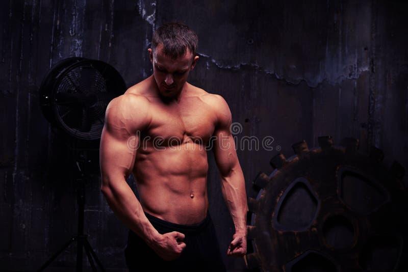 Den Shirtless sexiga mannen poserar mot väggen med stor rostig ge royaltyfri fotografi