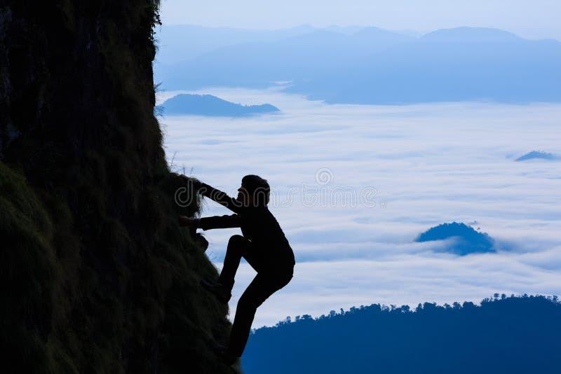 Affärsmannen klättrar ett berg arkivfoton