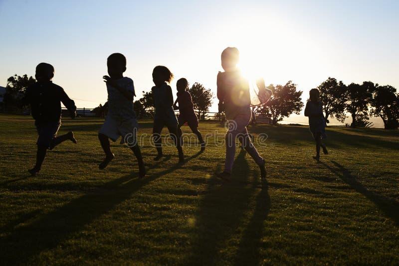 Den Silhouetted grundskolan lurar spring i ett fält royaltyfria foton