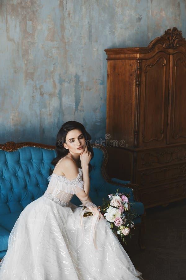 Den sinnlig och brunettmodellflickan med ljus makeup i innegrej snör åt klänningen med nakna skuldror med lyx fotografering för bildbyråer