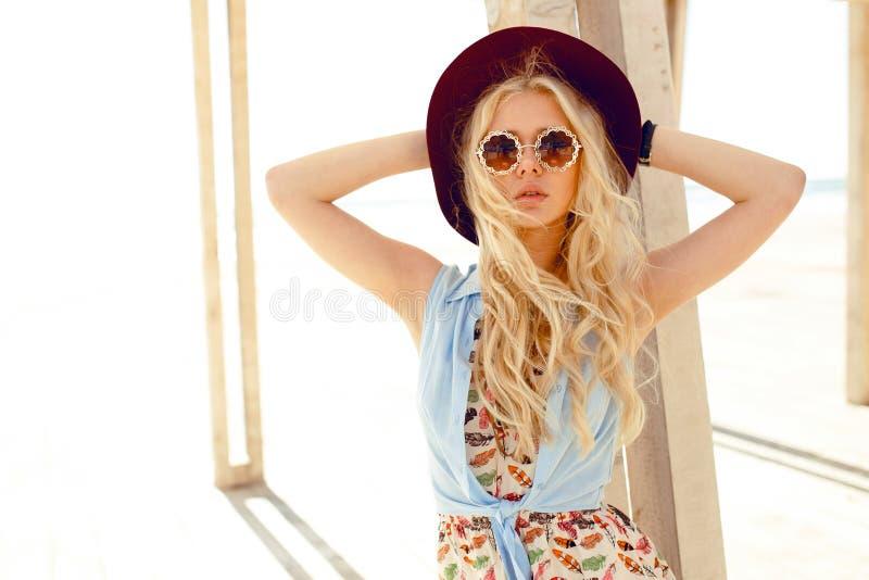 Den sinnliga blonda flickan med rund solglasögon, gullig klänning, våghår och den burgundy hatten, tycker om solljuset på havet arkivbilder