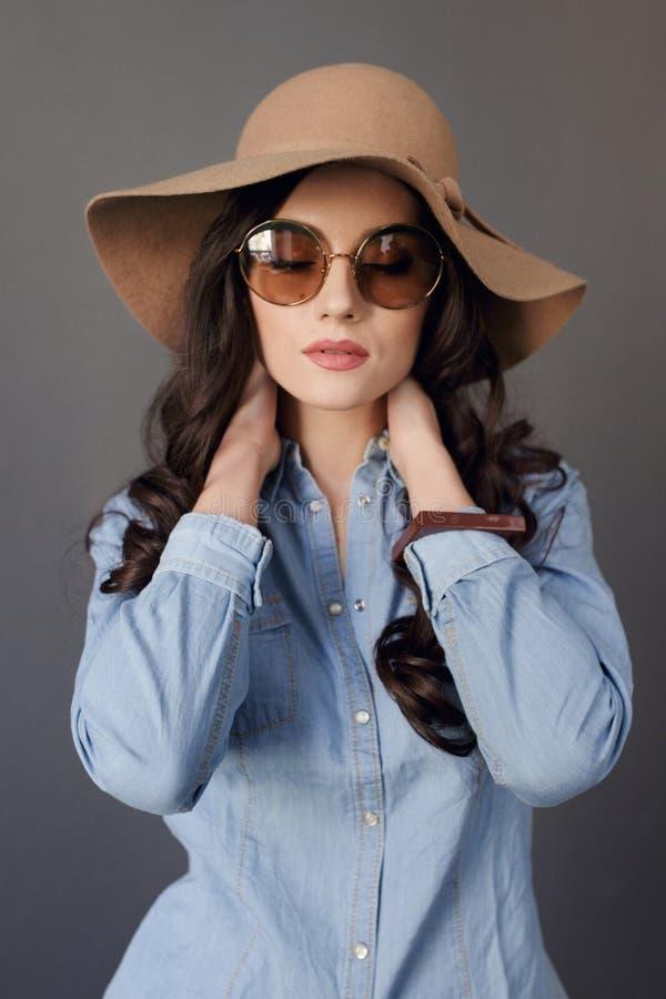 Den sinnliga brunettmodellen med rund solglasögon, lockigt hår och att bära i jeansskjorta och beige hatt, trycker på hans hals royaltyfria bilder