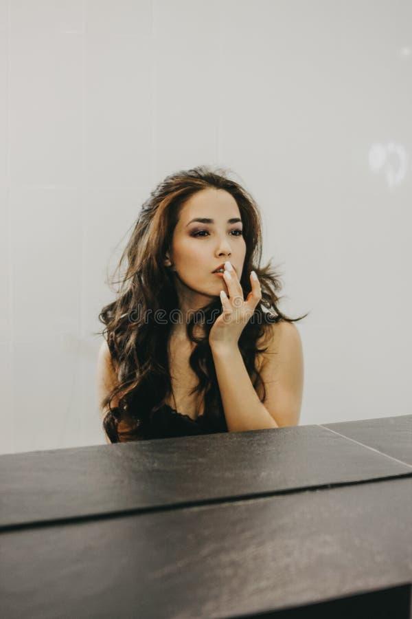 Den sinnliga härliga asiatiska unga kvinnan med mörkt långt hår korrigerar makeup framme av spegeln arkivfoton
