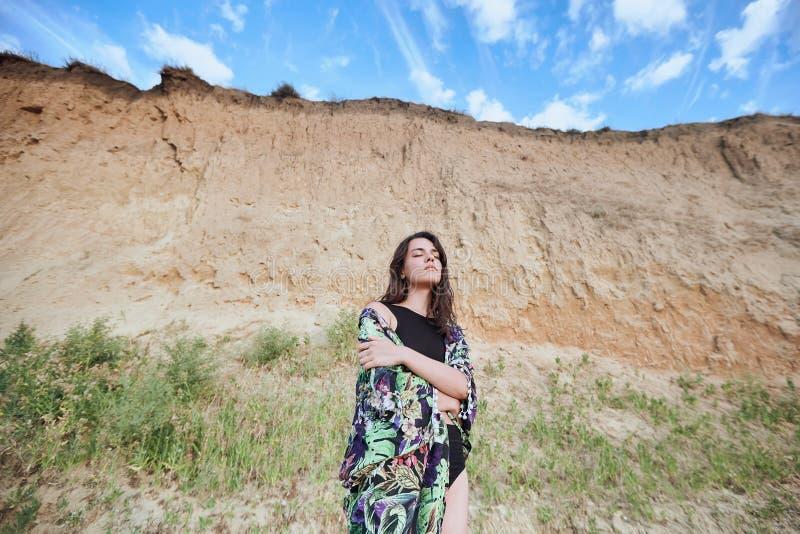 Den sinnliga härliga flickan som nära poserar, vaggar på den sandiga stranden Brunbr?nd ung kvinna p? sommarsemester arkivfoto