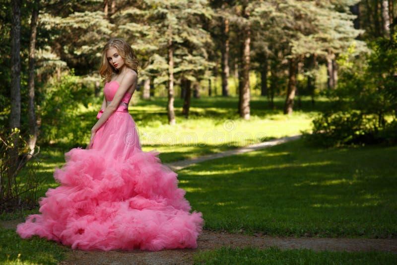Den sinnliga kvinnan i rosa aftonklänning med den fluffiga kjolen poserar i botanisk trädgård på gräset som omges av träna arkivbild