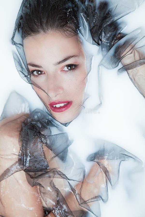 Den sinnliga kvinnaståenden med svart tyll mjölkar in badet royaltyfria bilder