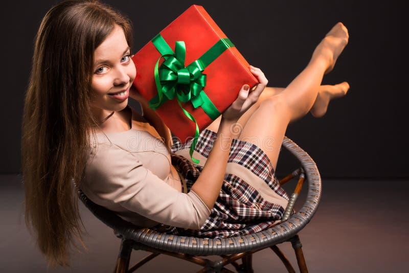 Den sinnliga sexiga attraktiva flickan sitter på en stol med arkivbild