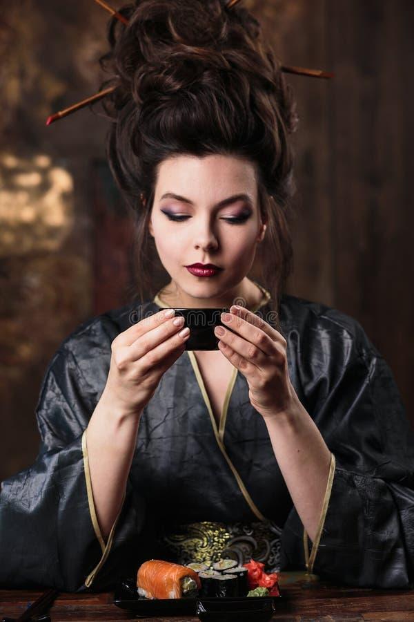 Den sinnliga unga kvinnan i en asiatisk dräkt för geisha med modemakeup och hårstil dricker te och äter sushi royaltyfria foton